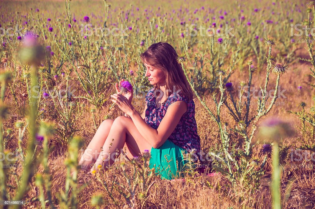 Romantic woman sitting in the field with a flower Lizenzfreies stock-foto