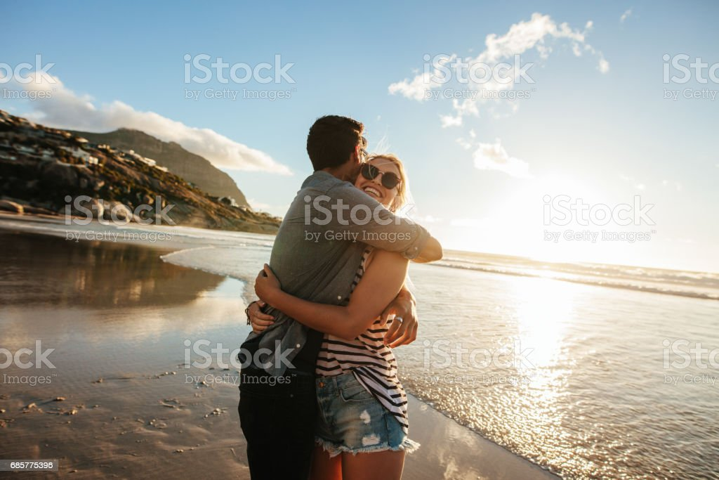 Romantic young couple embracing on beach royalty-free stock photo