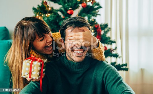 Beautiful young woman is standing behind her boyfriend with a gift in one hand and covered his eyes with the other hand.