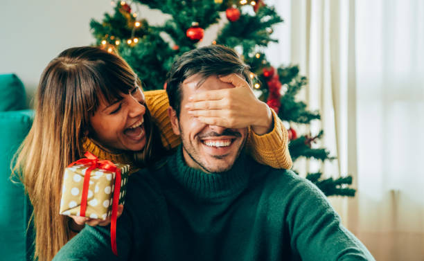 romantic young couple exchanging christmas gifts - regalo natale foto e immagini stock