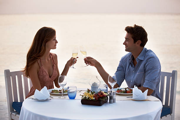 Romantic young couple having dinner in the beach stock photo