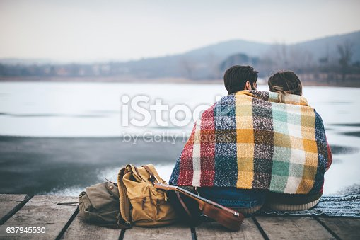Couple on cold winter day in nature, having fun