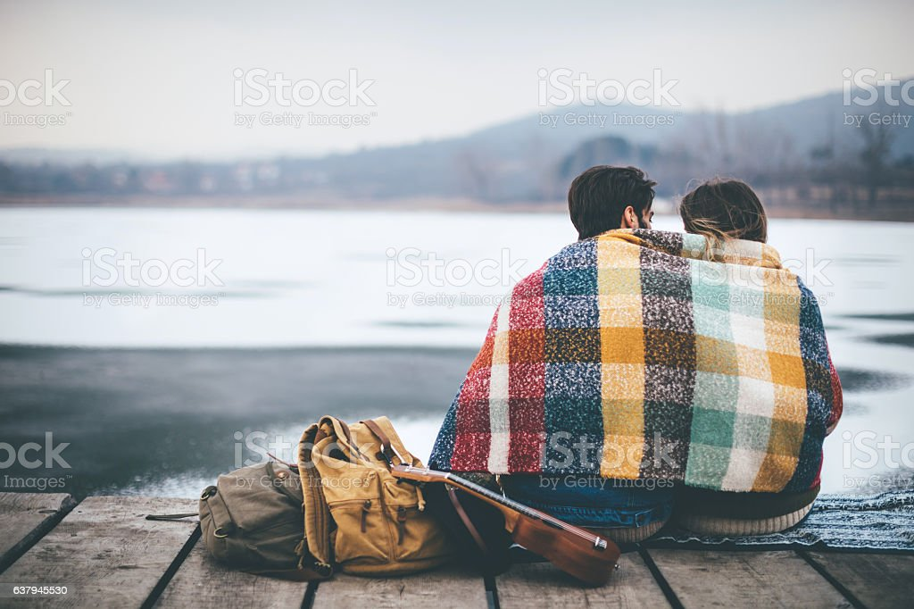 Romantic Young couple hugging by the lake in winter stock photo