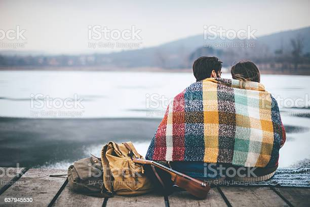 Photo of Romantic Young couple hugging by the lake in winter