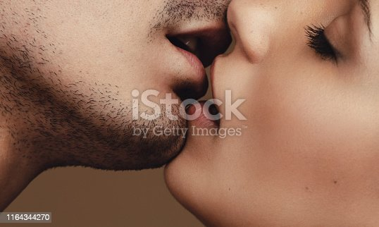 Close up of young man and woman kissing. Close up of a romantic young couple kissing with eyes closed.