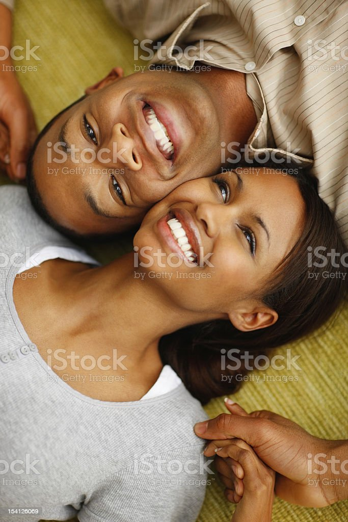 Romantic young couple lying together and smiling royalty-free stock photo