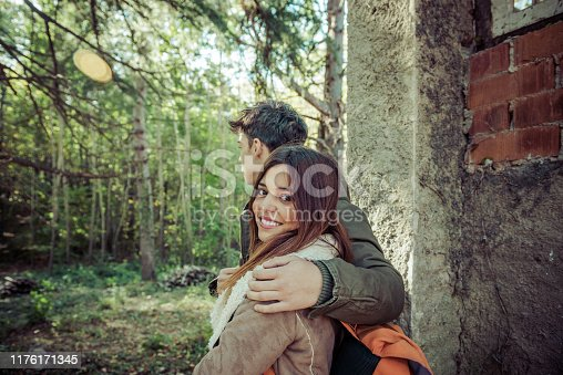 Trendy young couple of sightseers enjoying a trip in the woods.