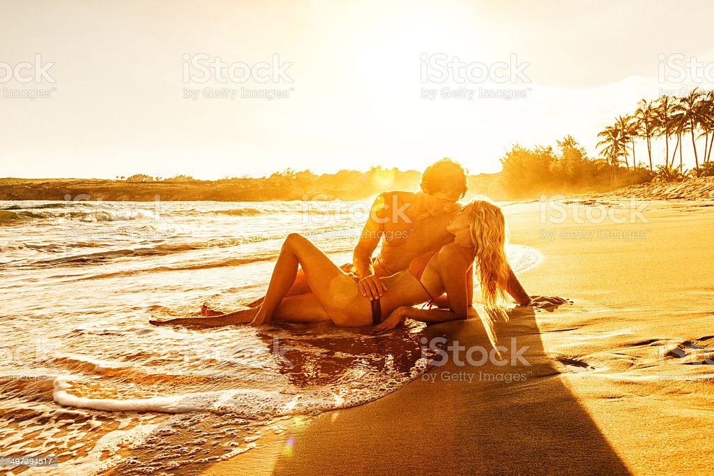 Romantic Young Couple on Beach at Sunset stock photo