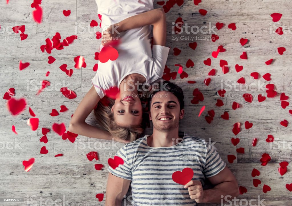 Romantic young couple Top view of beautiful young couple holding red paper hearts, looking at camera and smiling while lying on the floor Adult Stock Photo