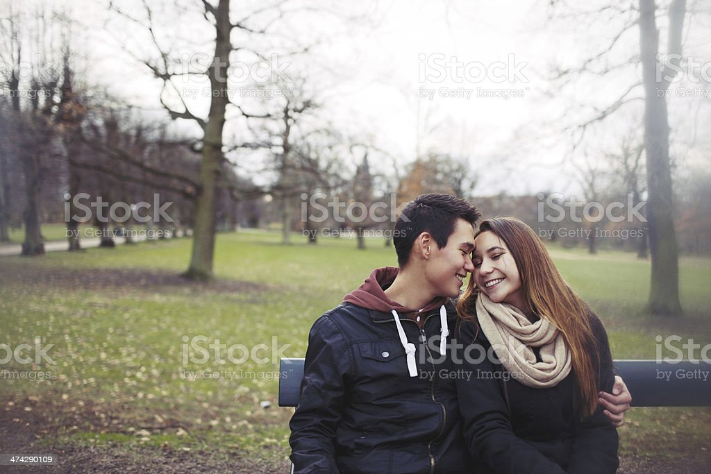 Romantic young couple sitting on a park bench stock photo