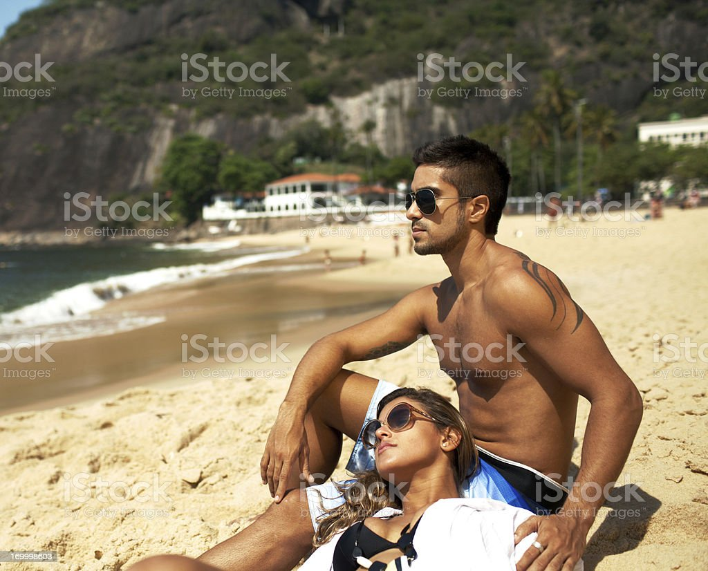 Romantic young couple sitting on the beach enjoying warm sun. royalty-free stock photo