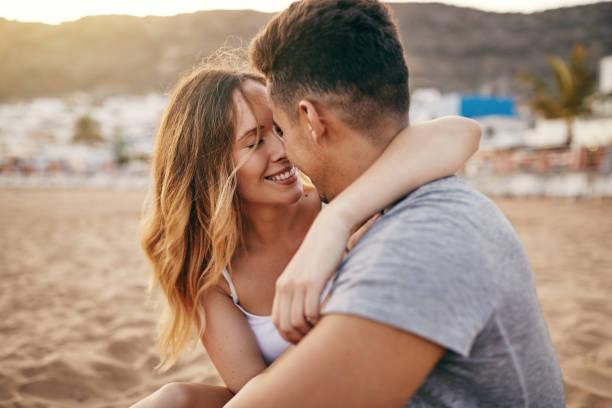 romantisch jong koppel zittend samen op een zandstrand - verliefd worden stockfoto's en -beelden