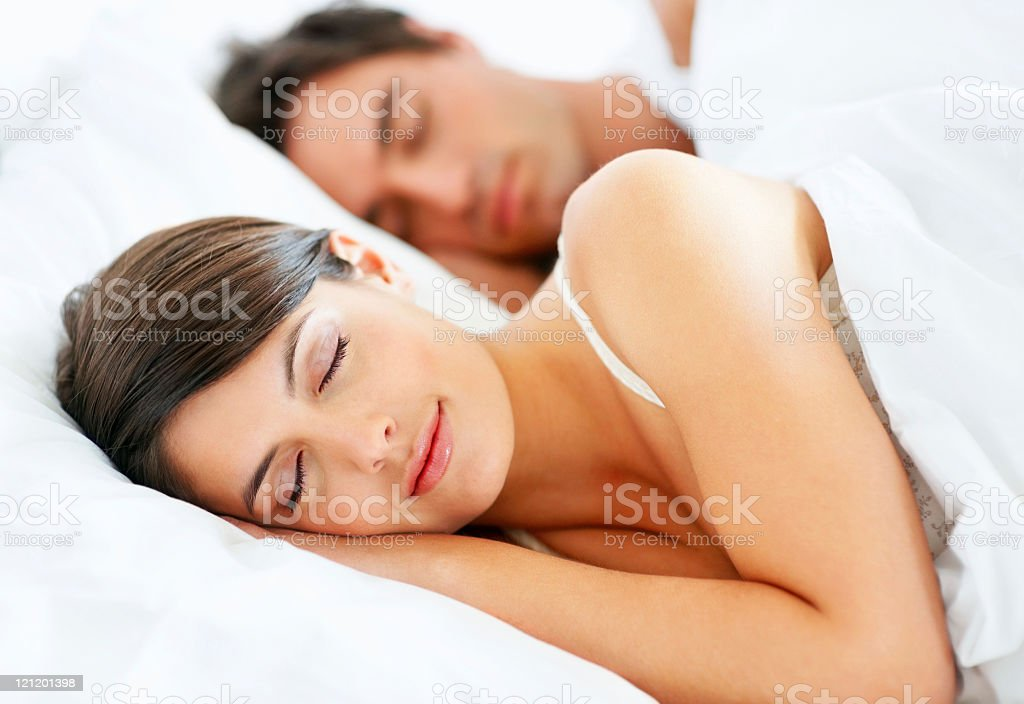 Romantic young couple sleeping in bed stock photo