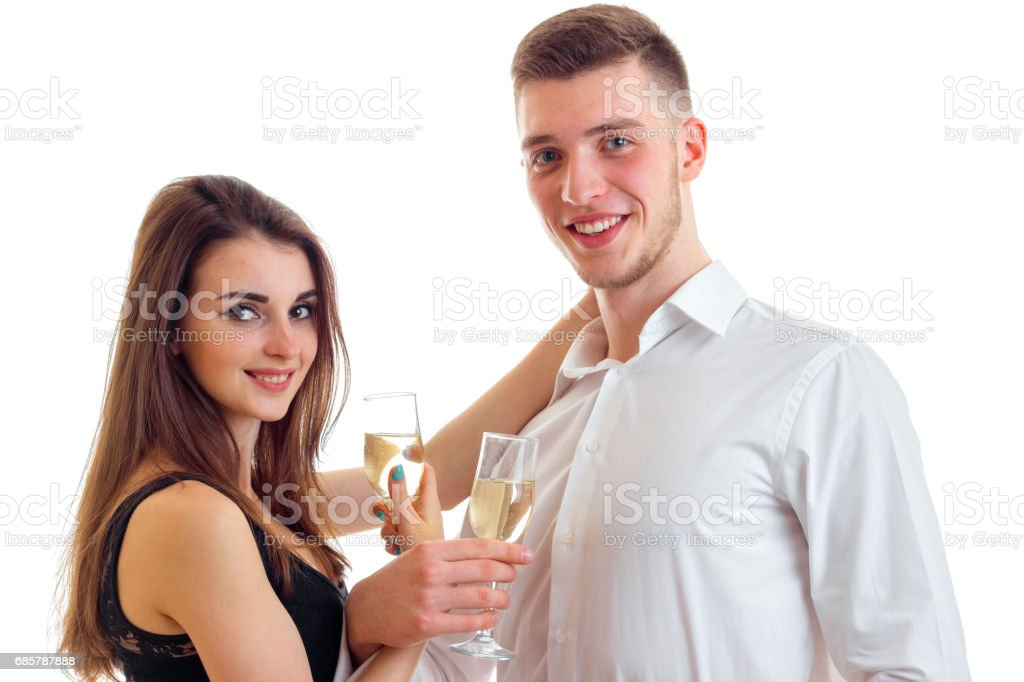 romantic young couple smiling look forward and carrying champagne glasses isolated on a white background stock photo