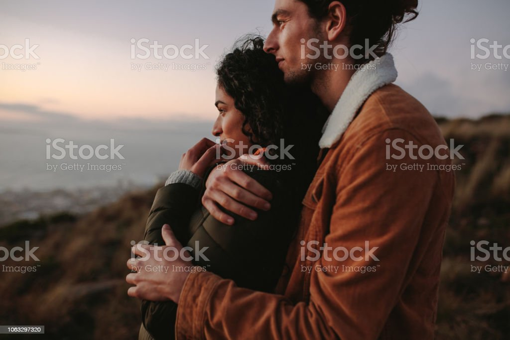 Romantic young couple standing in mountain Romantic young couple standing in mountain together and looking at view. Young man embracing his girlfriend and looking away. Adult Stock Photo