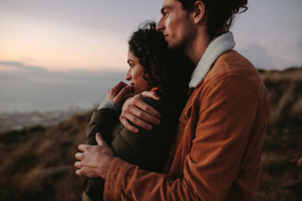 Romantic young couple standing in mountain Romantic young couple standing in mountain together and looking at view. Young man embracing his girlfriend and looking away. amor stock pictures, royalty-free photos & images