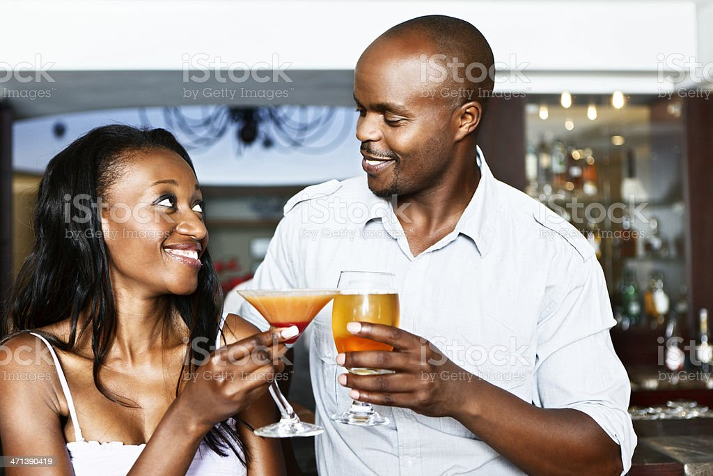 Romantic young couple toasting each other in cocktails at bar royalty-free stock photo