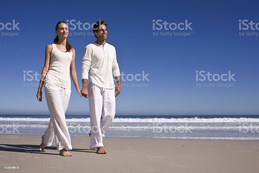 Romantic young couple walking together at beach royalty-free stock photo