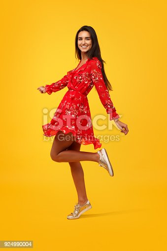 Bright charming female in red flying dress dancing on orange background smiling at camera.