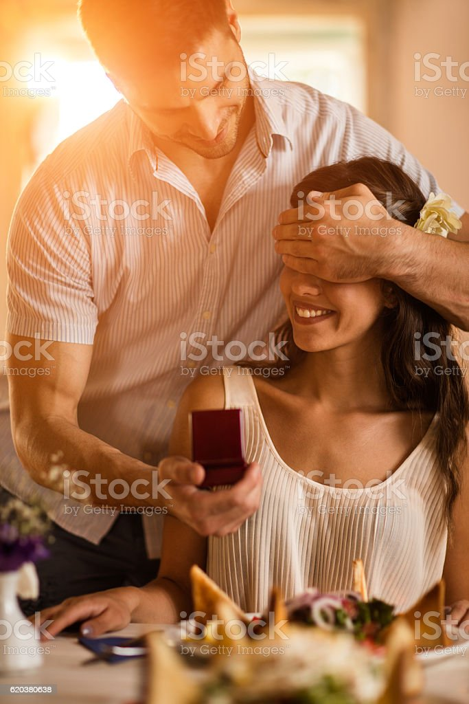 Romantic young man surprising his girlfriend with ring box. foto de stock royalty-free