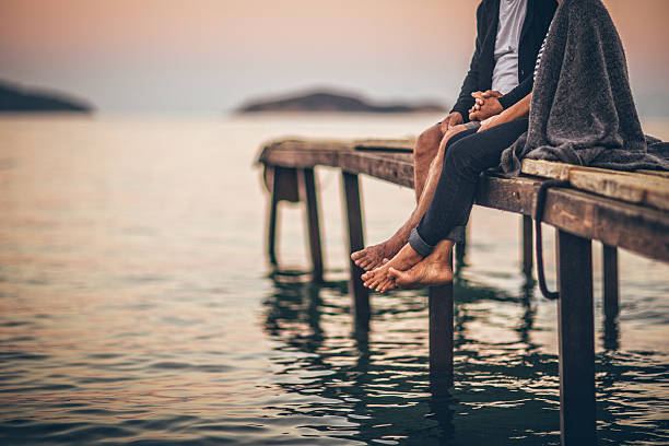 romantics on the dock - old man feet stock photos and pictures