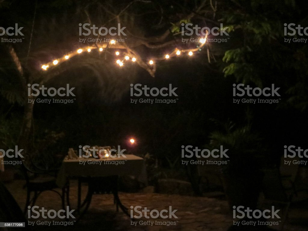 Romatic dinner table lit by fairy lights stock photo