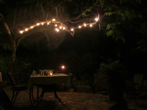 romantisches abendessen am tisch, beleuchtet von lichterketten - terrassen lichterketten stock-fotos und bilder