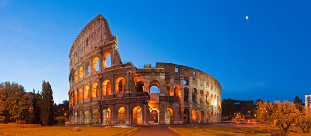 Rome Coliseum Colosseo ancient roman amphitheatre Italy panorama blue moon Deep blue dawn skies and setting moon over the iconic arches and illuminated arcades of the ancient Roman Coliseum in this dramatic dawn panorama from the heart of Rome, Italy. ProPhoto RGB profile for maximum color fidelity and gamut. palatine hill rome stock pictures, royalty-free photos & images