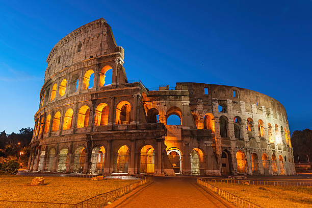 Rome Colosseum ancient amphitheatre illuminated at dawn Deep blue skies and white stars over the iconic arches and illuminated arcades of the ancient Roman Coliseum in this dramatic dawn vista from the heart of Rome, Italy. ProPhoto RGB profile for maximum color fidelity and gamut. palatine hill rome stock pictures, royalty-free photos & images