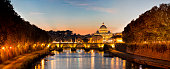 Panorama of St. Peter's Basilica at dusk, Tiber river and Ponte Sant'Angelo bridge are seen in the foreground, Italy.