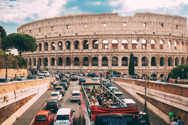 Rome, Italy. Colosseum. Red Hop On Hop Off Touristic Bus For Sightseeing In Street Near Flavian Amphitheatre. Famous World UNESCO Landmark. City Sightseeing Tour. stock photo