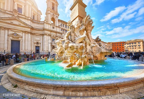 Rome, Italy. Fountain of the Four Rivers on Piazza Navona. Ancient fountain, statues, obelisk design of Bernini. Famous landmark touristic location near Sant Agnese in Agone church. Sunny summery day.