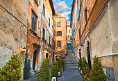 Rome, Italy. Yard of old street in downtown with antique building and stone stairs. Evening cityscape with street lamps on walls and decorative plants in flowerpots.