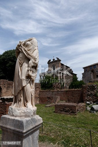 sculpture of vestal, Forum Roman, in background temple of Antoninus and Faustina, Rome, Italy