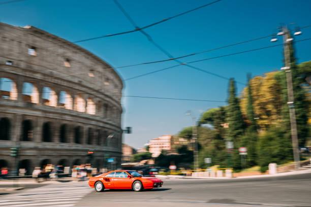 rome, italy. red ferrari mondial coupe in fast motion near colosseum. - colosseo 1900 foto e immagini stock