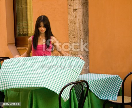 istock Rome, Italy: Restauant Worker with Checked Tablecloth 1037783930