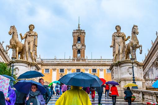 Rome, Italy - November 04 2018: Statues of Pollux & Castor at the Cordonata Stairs at Piazza del Campidoglio (Capitol Square) on Capitoline Hill, 1 of Rome's 7 hills. Palazzo Senatorio in background.