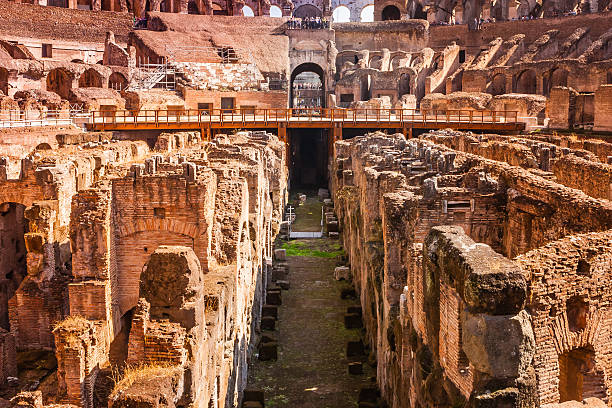 Rome, Italy: The Collapsed Interior Floor Of The Colosseum Exposing The Hypogeum Or Underground Sections The horrific interior of the Colosseum in Rome. The Colosseum is an elliptical amphitheathre. It is considered one of the greatest works of Roman engineering and architecture. Originally the Flavian Amphitheatre, construction of the Colosseum began under the rule of the Emperor Vespasian in around 70 - 72 AD. The top level was finished and inaugurated in 80 AD by his son Titus. Over 9000 wild animals were said to have been killed during the inaugural games. The photo shows some aspects of the hypogeum or underground sections. The floor on which the Gladiators fought for their lives to entertain the ancient Romans, has completely collapsed, exposing the lower level where gladiators and animals were held. Photo shot in the afternoon sunlight; horizontal format.  chandra dhas, stock pictures, royalty-free photos & images