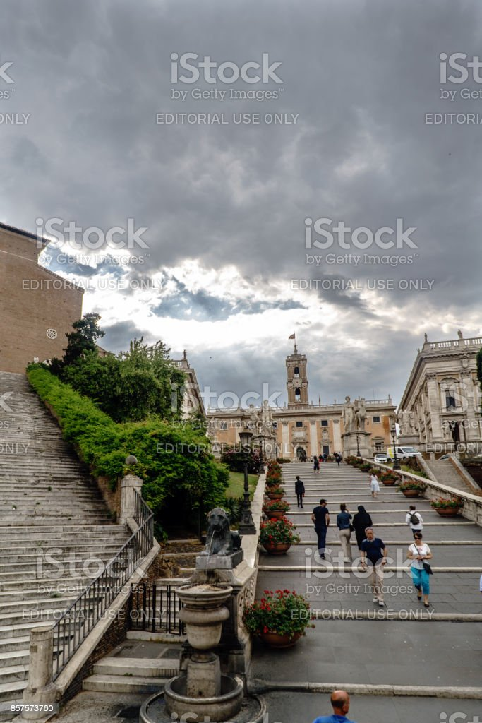 Rome, Lazio, Italy. July 20, 2017.Road access staircase called 'Palazzo Senatorio' with people climbing through it and sky with dramatic black clouds stock photo