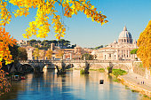 The sun setting over the river Tiber in Rome, with the arches of Ponte Sant'Angelo and the dome of St Peter's Basilica in the distance.