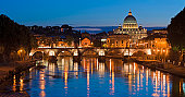 St. Peter's cathedral over bridge and river with flowers in Rome, Italy