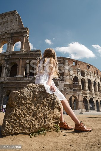 Rome, Italy - September 26, 2013: Rear view of teenage girl in white dress sitting on rock at Coliseum under blue sky.