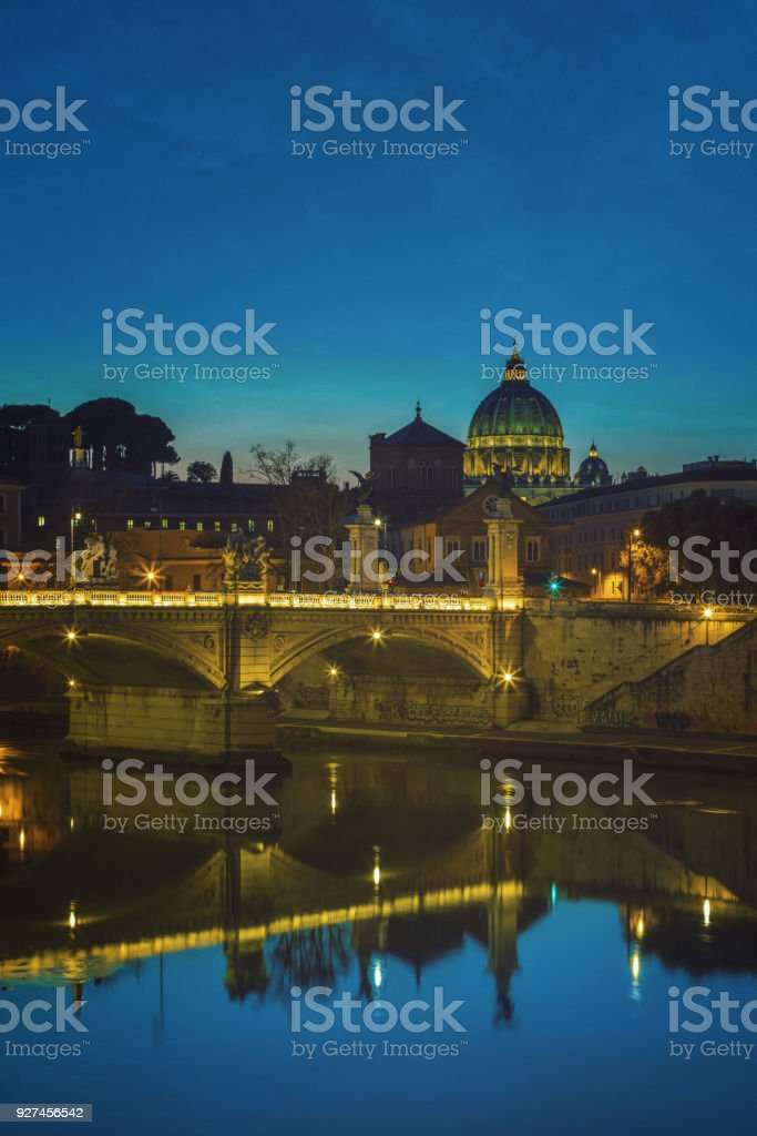 Rome: Tiber river with Ponte Vittorio Emanuele II, the lit dome of St. Peter's Basilica in the background stock photo