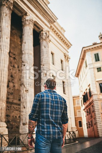 Cropped shot of an unrecognizable man standing alone and looking at an ancient building during a day out in Rome