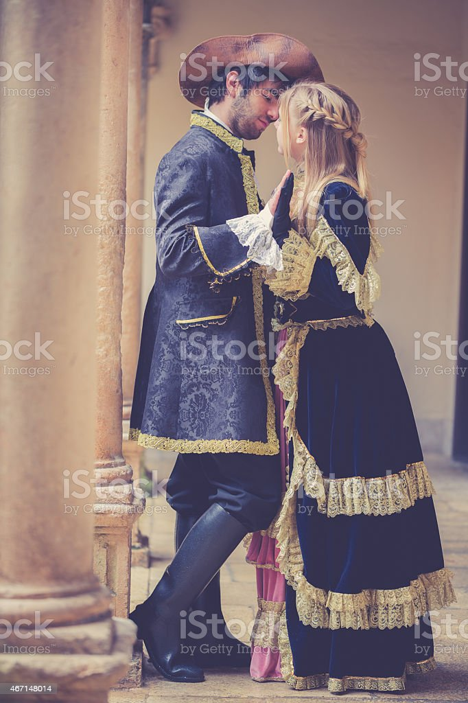 romeo and juliet holding hands at balcony stock photo