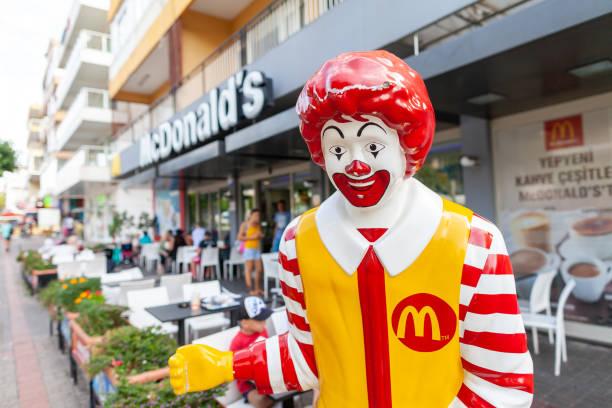 ronald mc donald mascot stands in front of a mc donalds shop in antalya - mcdonalds стоковые фото и изображения