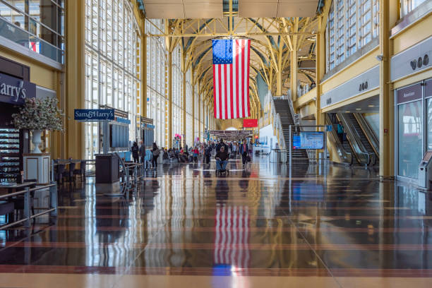 Ronald Reagan Washington National Airport Washington, DC, United States - March 26, 2019: Ronald Reagan Washington National Airport view,  A giant flag hangs above travelers in the hall of the Ronald Reagan Washington National Airport in Washington, DC.USA. ronald reagan washington national airport stock pictures, royalty-free photos & images