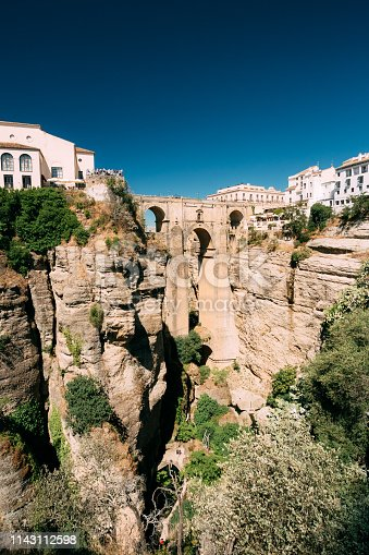 Ronda, Province Of Malaga, Spain. Puente Nuevo (New Bridge) is newest and largest of three bridges that span the 120-metre (390 ft)-deep chasm that carries the Guadalevin River and divides city of Ronda, Province Of Malaga, Spain