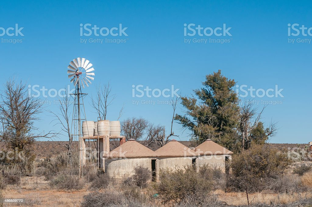 Rondavels next to a windpump and water storage tanks stock photo