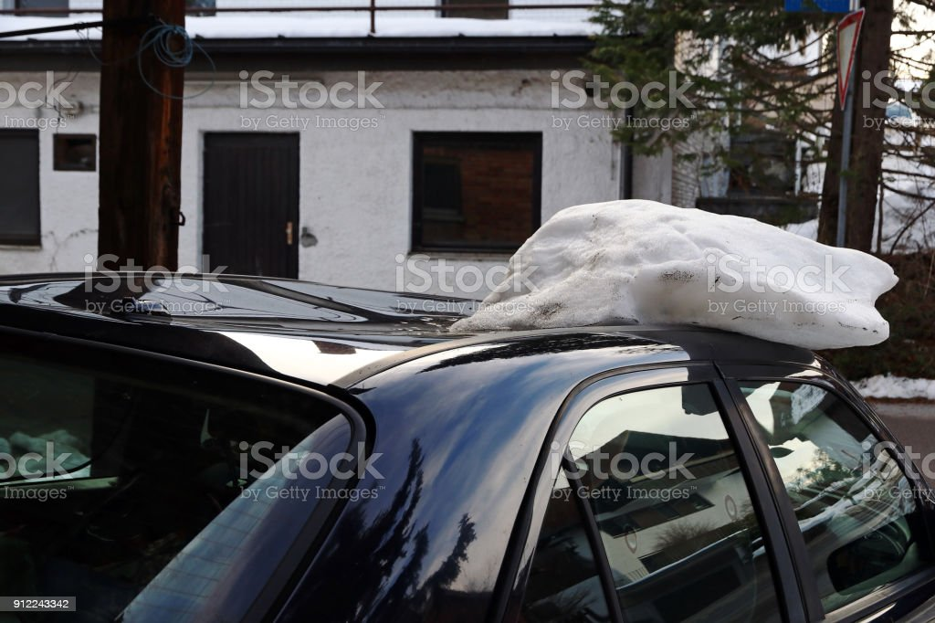 A roof avalanche damaged a black car on the roof. Avalanche of roof damage to a car stock photo